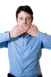 Speak no evil. Business man with blue shirt holding both hands in front of his mouth to prevent him from speaking Stock Image