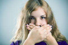 Speak no evil. Portrait of young girl holding hands on mouth stock image