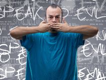 Speak no evil. Conceptual front view portrait of a man covering his mouth with his hands while looking at camera against gray background with speak no evil Royalty Free Stock Photos