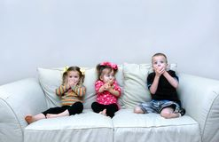 Speak no Evil. Three small children sit on a couch in their home, and cover their mouths with their hands.  They are pretending to speak no evil Stock Photo