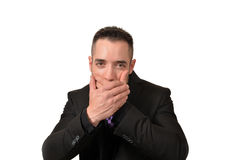 Speak no evil. A young man covering his mouth in a speak no evil pose Royalty Free Stock Photos