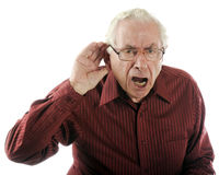 Speak up, I Can't Hear You!. A senior man looking grumpy as he calls out and strains to here stock photo