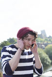 Speak up, I can't hear you. A young man uses his mobile phone outdoors. He is holding his phone to one ear and his hand to his other try and hear the person royalty free stock photography