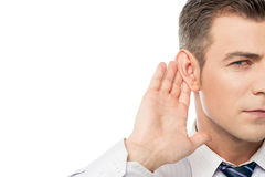 Speak up please i can't hear you !. Young businessman holds his hand near ear royalty free stock images