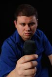 Speaker. Man holding a microphone contemplating what he should say Stock Photography