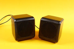 Speaker. A pair of speakers in black on a Yellow background Stock Photo