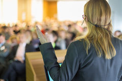 Speaker at Business Conference and Presentation. Female speaker at Business Conference and Presentation. Audience at the conference hall. Business and Royalty Free Stock Image