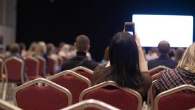 People listen to the presentation the conference hall. Back view. Empty chairs stock video footage