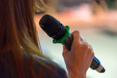 Speaker at conference holding microphone. In the hand royalty free stock photography