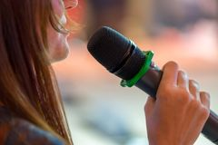 Speaker at conference holding microphone. In the hand stock photography
