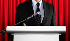 Free Speaker Giving Speech At Seminar With Red Curtain Background Royalty Free Stock Photo - 115693175