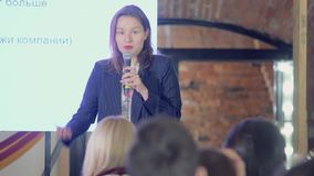 Speaker is giving speech at business event. Adult businesswoman in modern conference hall. Business and entrepreneurship seminar stock video footage