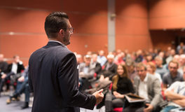 Speaker giving talk at business conference event. Audience at conference hall. Business and Entrepreneurship concept Stock Photography