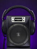 Speaker and headphone set. A speaker and a headphone set over a purple background Stock Photography