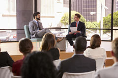 Speaker and interviewer in front of audience at a seminar royalty free stock photo