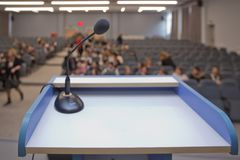 Speaker prepare before speaking to the audience behind the podium focused microphone on the podium and blurred empty seat and some stock photography