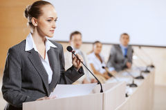 Speaker at stage. Businesswoman standing on stage and reporting for audience royalty free stock photography