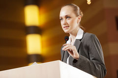 Speaker at stage. Businesswoman standing on stage and reporting for audience stock photos