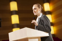 Speaker at stage. Businesswoman standing on stage and reporting for audience royalty free stock images