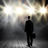 Speaker on stage. Rear view of businessman standing in lights of stage stock photo