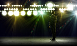 Speaker on stage. Rear view of businessman standing in lights of stage Stock Image