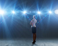 Speaker on stage. Rear view of businesswoman standing in lights of stage royalty free stock images