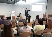 Speaker standing and lecturing on business conference in meeting hall stock images