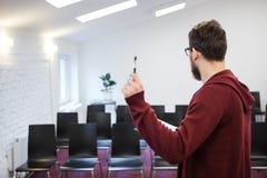 Speaker standing in white conference room. Backside. Speaker in glasses with beard standing in white conference room. Backside royalty free stock image