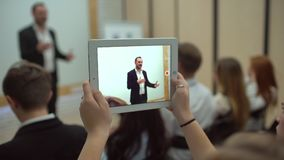 Men hand using tablet computer at a business meeting, seminar or lecture. 4 k Professional coach speaking at workshop stock video footage