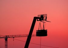 Speakers and Lift silhouette. A set of concert speakers suspended from a forklift are silhouetted by a red sky.  A large construction crane is in the distance Stock Images