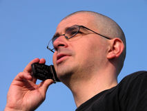Speaking. Young bald-headed man speaking to the mobile phone Stock Photo