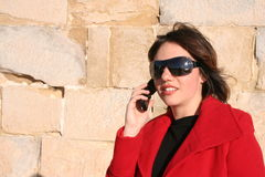 Speaking. Young woman in a red jacket speaking on the phone Royalty Free Stock Photo