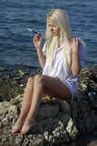 Speaking blonde with a cigarette near sea Stock Photos
