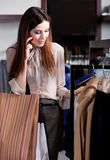 Speaking on the cellphone and choosing clothes Stock Photo