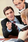 Speaking man. Portrait of handsome businessman explaining something to his colleagues with smart woman near by Royalty Free Stock Image