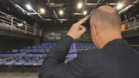 Speaking man knocking finger on forehead back view during performance on stage. Pensive man touching forefinger on forehead public speaking in meeting hall stock video footage