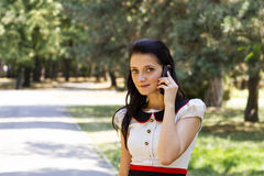 Speaking on mobile phone. Beautiful young woman speaking on mobile phone on park alley during summer Royalty Free Stock Images