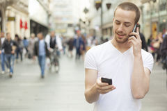Speaking on mobile phone and second in hand Royalty Free Stock Photos