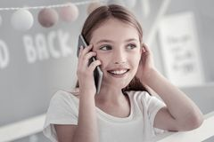 Pretty gleeful girl talking on the phone royalty free stock photography