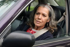 Speaking out from the car. A mature woman speaking to someone else on the road, her door open as if ready to get out. Concern for driving safety and hazards Stock Images