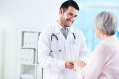 Speaking with patient. Confident doctor looking at his senior patient while speaking to her Stock Photography