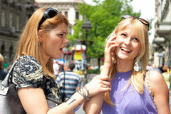 Speaking by phone. Woman warning her friend to stop speaking by phone Royalty Free Stock Images
