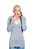 Speaking on phone shocked woman. Covers her mouth with hand, isolated on white Royalty Free Stock Image