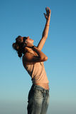 Speaking with the skies. Young woman speaking on mobile phone looking up to the sky Stock Photo