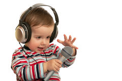 Speaking toddler with headphones and microphone. A speaking toddler with headphones and microphone; isolated on the white background Royalty Free Stock Images