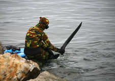 Spear Fisherman Mission Bay. A spear fisherman, wearing a camouflauge wetsuit, donns fins preparing to enter the cold channel waters at the entrance to Mission Stock Photo