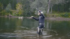Spear fisherman out of the water and shows Freshwater Fish at spear of underwater fisherman after hunting in forest. River, wide angle stock video