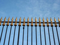 Spear head property railings. Ornamental spear headed wrought iron black and gilded property railings against a bright blue sky Stock Photography