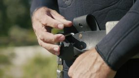 Spear underwater fisherman wearing belt with weights, preparing for hunt. Close up stock footage