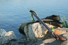 Spearfishing gear - fins, speargun on a sea rock against blue s stock image